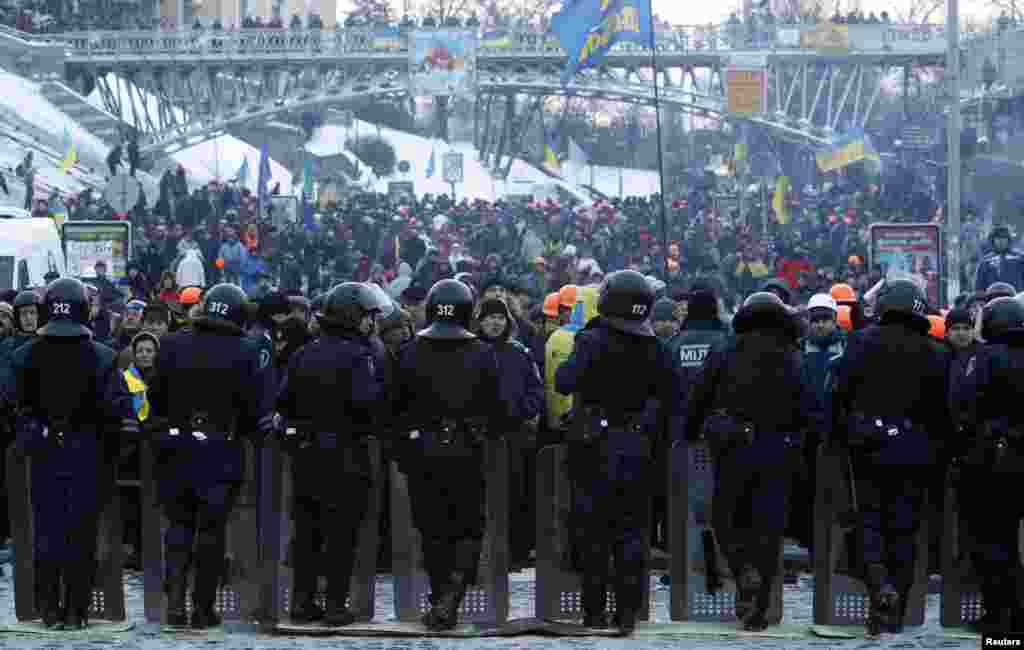 Protesters stand in front of riot police near Independence Square in Kyiv, Dec. 11, 2013.