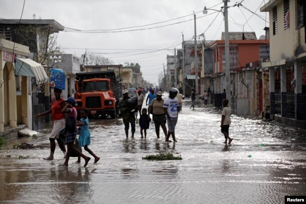 Residents walk on a flooded street after Hurricane Matthew in Les Cayes, Haiti, October 5, 2016.