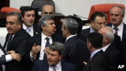 FILE - Turkish legislators from Prime Minister Recep Tayyip Erdogan's ruling party and the main opposition Republican People's Party brawl during a tense all-night debate over a controversial law on changes to a council that appoints and overseas judges a