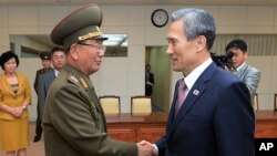 In this photo provided by the South Korean Unification Ministry, South Korean presidential security adviser Kim Kwan-jin, right, shakes hands with Hwang Pyong So, North Korea's top political officer for the Korean People's Army, after their meeting at the
