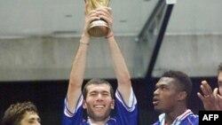 Les joueurs français Bixente Lizarazu (L) et Marcel Desailly (R) sourient alors que Zinedine Zidane détient le trophée, après la finale de la Coupe du monde 1998 entre la France et le Brésil, au Stade de France à Saint-Denis, le 12 juillet 1998.