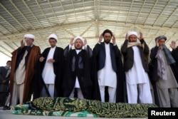 Afghans offer funeral prayers behind the body of a civilian killed in Sunday's deadly suicide attack at a voter registration center, in Kabul, Afghanistan, April 23, 2018.