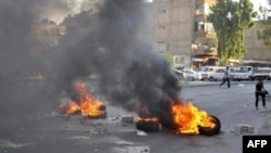 A handout picture released by the Syrian opposition's Shaam News Network on July 17, 2012 shows opponents of the regime blocking the roads with burning tires in Damascus on July 16, 2012.