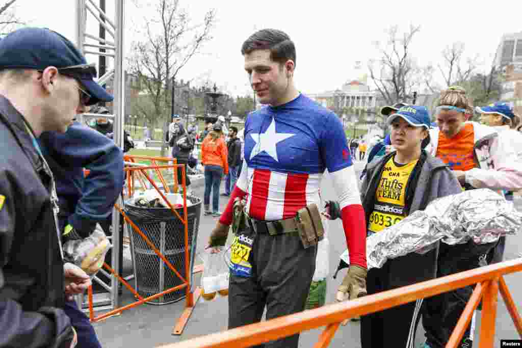 Marathon participant Christopher Snedecor of Somerville, MA goes through security as he arrives at the Boston Commons to board a bus that will bring him to the marathon starting line in Hopkinton, April 20, 2015.