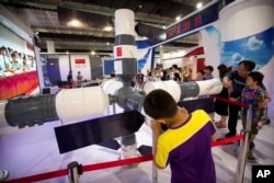 "FILE - Visitors look at a model of China's Tiangong-1 space station at the China Beijing International High-Tech Expo in Beijing, June 10, 2017. China was excluded from the International Space Station largely due to concerns over its space program's connections to the military and U.S. legislation barring such cooperation. That didn't stop the country from launching its own space laboratory in 2011, named Tiangong (""Heavenly Palace""), which orbited Earth until last April."