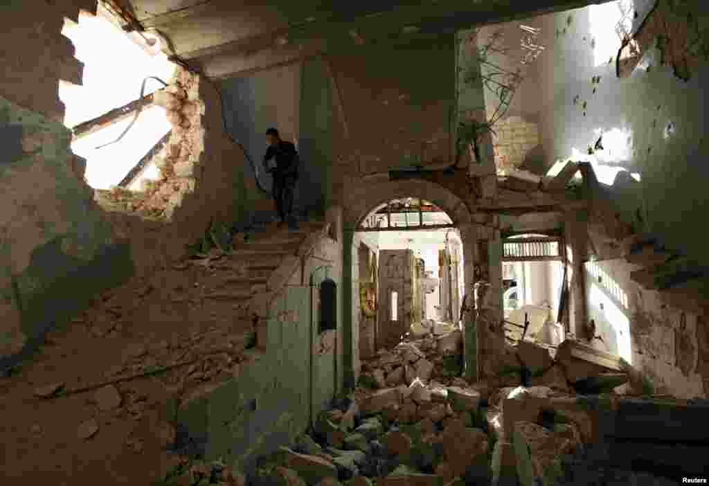 A Free Syrian Army fighter carries his weapon as he walks down the stairs of the damaged former Immigration and Passport building in Aleppo, Syria.