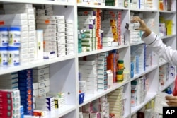 FILE - In this Nov. 5, 2018 file photo, a drugstore employee reaches for medicine from shelf in downtown Tehran, Iran. According to a study published in the British journal Lancet on Thursday, Aug. 22, 2019, researchers say a cheap daily pill that combine