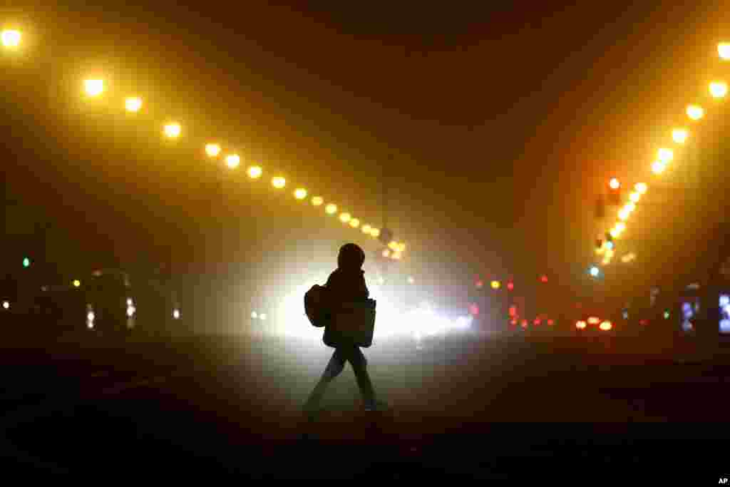 A woman crosses a road early morning in Munich. Germany has entered a harder lockdown, closing shops and schools in an effort to bring down stubbornly high new cases of the coronavirus.
