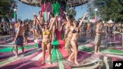 خانم های بیکینی پوش در یک جشنواره موسیقی در زیر فواره آب در شهر منچستر ایالت تنسی آمریکا