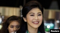 FILE - Former Thai Prime Minister Yingluck Shinawatra smiles as she arrives at Bangkok's Suvarnabhumi Airport, July 23, 2014.