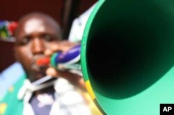Zimbabwean hawker Walter Kanyegoni blows a plastic vuvuzela trumpet he's painted in the colors of the South African flag