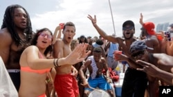 FILE - Spring breakers dance and sing to music in the South Beach area of Miami Beach, Florida, March 14, 2016.
