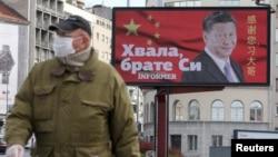 塞尔维亚一名戴着口罩的男子走过贝尔格莱德街头树立的感谢中国领导人习近平的广告牌旁。(2020年4月1日)