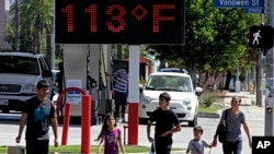 "FILE - Pedestrians walk past a digital thermometer reading 113 degrees Fahrenheit (45 degrees Celsius) in the Canoga Park section of Los Angeles, Aug. 15, 2015. ""The average surface air temperature for the year ending September 2016 is by far the highest since 1900,"" according to U.S. government data."