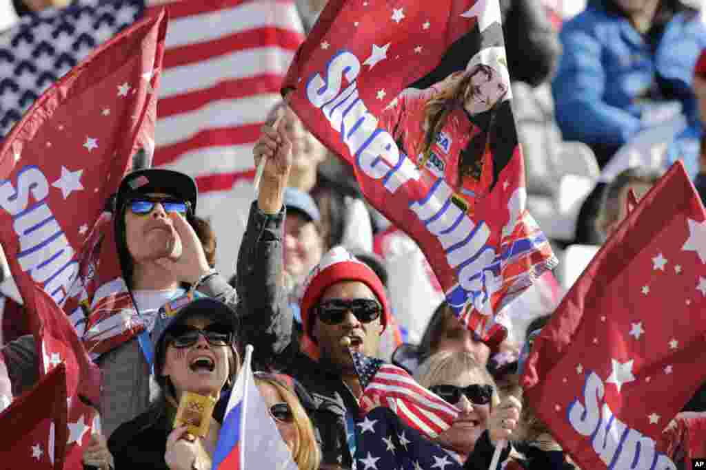 Fans wave flags for United States skier Julia Mancuso during the downhill portion of the women's supercombined,Krasnaya Polyana, Feb. 10, 2014.