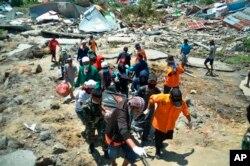پالو میں امدادی کارکن ملبے سے نکلنے والی نعشوں کی بیگز میں لے جا رہے ہیں۔ 2 اکتوبر