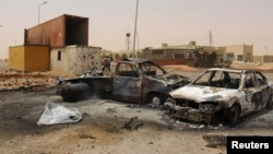 FILE - The wreckage of vehicles is seen after a suicide car bomber blew himself at a checkpoint near Misrata, Libya, May 21, 2015.