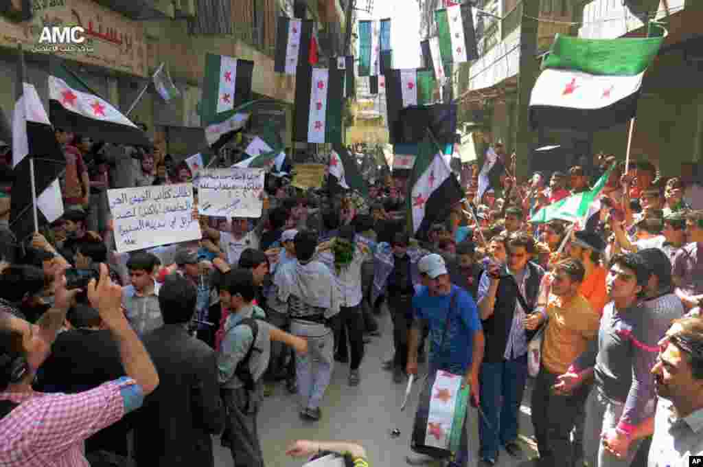 This citizen journalism image shows anti-Syrian regime protesters holding banners and waving the Syrian revolutionary flags, Aleppo, Syria, April 26, 2013. (Aleppo Media Center AMC)