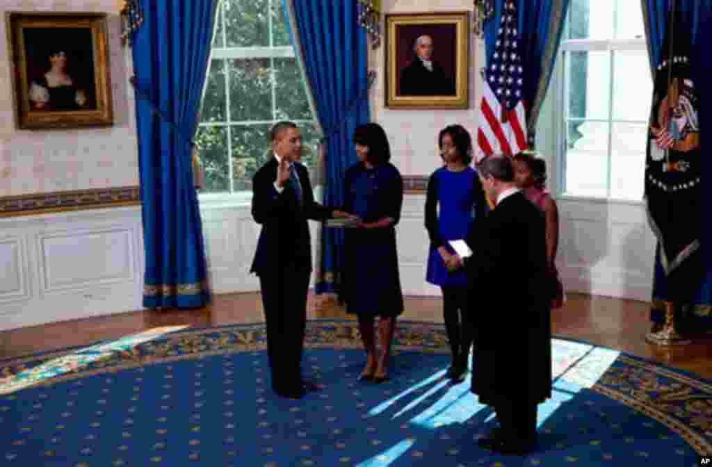 President Barack Obama takes the oath of office at the official swearing-in ceremony in the Blue Room of the White House in Washington, DC, Sunday, Jan. 20, 2013, holding the family bible is First Lady Michele Obama, administering the oath is Supreme Cour
