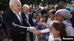 Les sénateurs McCain (à g.) et Lieberman saluent des enfants dans un camp de réfugiés près de la frontière turco-syrienne, le 10 avril 2012.