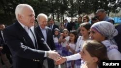 Les sénateurs McCain (à g.) et Lieberman saluent des enfants dans un camp de réfugiés près de la frontière turco-syrienne (10 avril 2012)