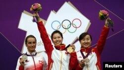 Atlet tembak perempuan Tiongkok Yi Siling (tengah) memenangkan medali emas pertama olimpiade (28/7). Qatar mengirimkan atlet perempuan pertama yang mengikuti cabang olahraga menembak.
