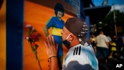 A soccer fan kisses a poster of Diego Maradona at the entrance of the Boca Juniors stadium, known as La Bombomera, in Buenos Aires, Argentina, Nov. 25, 2020.