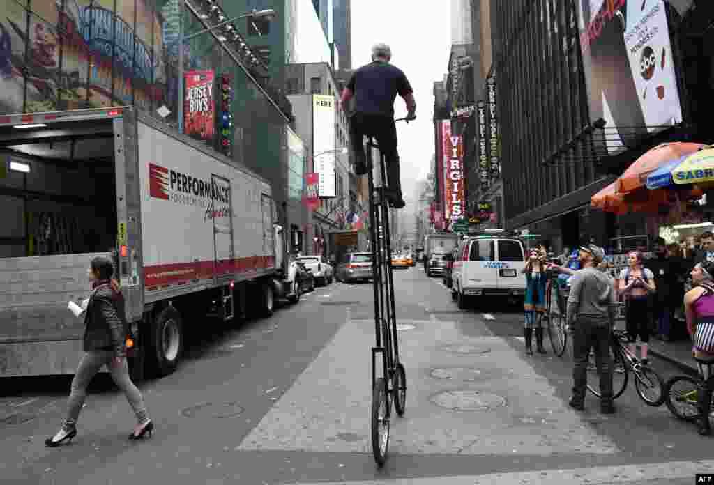 یکی از بازیگران نمایش سرکس در نیویارک برای جلب تماشاچیان بیشتر در حال گردش با یک بایسکل منحصر به فرد در شهر نیویارک