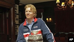 Two-time Davis Cup champion Jim Courier, who signed a multi-year agreement to lead the U.S. Davis Cup team, is shown with a replica of the Davis Cup after the United States Tennis Association made the announcement in New York, Oct 27, 2010