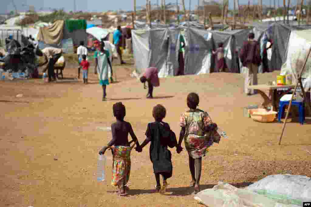 Three children walk through a spontaneous camp for internally displaced persons at the United Nations Mission to South Sudan (UNMISS) base in Juba, Jan. 9, 2014.