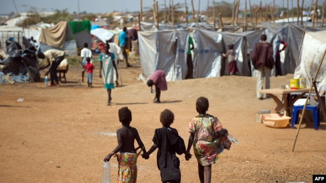 Three children walk through a camp for internally displaced persons at the United Nations Mission to South Sudan (UNMISS) base in Juba,  Jan. 9, 2014.