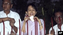 Pemimpin pro-demokrasi Myanmar Aung San Suu Kyi, bersama para pejabat partainya, berbicara kepada para pendukung dari balik gerbang besi rumahnya di Yangon, 2010. (Foto: Dok)