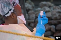 FILE - A nurse prepares a vaccine against Ebola in Goma, DRC, Aug. 7, 2019.