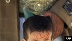 Một bé trai Yemen với dòng chữ viết trên mặt 'hãy ra đi', đứng cạnh cha trong cuộc biểu tình đòi Tổng thống Saleh từ chức