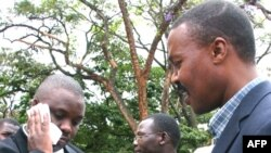 FILE - Erias Lukwago (L) walks with Forum for Democratic Change (FDC) representative Maj. Gen. Mugisha Muntu (R).
