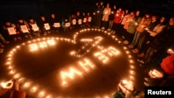 FILE - Participants of a vigil light candles during a tribute to passengers of missing Malaysia Airlines flight MH370, in Yangzhou, Jiangsu province, March 13, 2014.