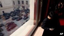 2013年3月5日中国在北京举行第十二届人大开幕式之后,当政府官员的车辆准备离开人民大会堂的时候,一名人大代表查看他的手机。