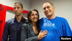 Felix Baez, right, appears with wife Vania Ferrer and son Alejandro Baez at a news conference in Havana, Dec. 6, 2014.