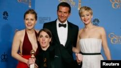 《美国骗局》演员艾米•亚当斯(左)、布莱德利•库珀与珍妮佛•劳伦斯(右)手捧金球在后台与制片人梅根•埃里森合影。