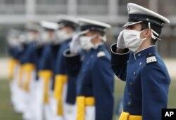 Para kadet yang mengenakan masker memberi hormat pada upacara kelulusan untuk Kelas 2020 di Akademi Angkatan Udara A.S., Sabtu, 18 April 2020, di Akademi Angkatan Udara, selama wabah corona. (Foto: AP)