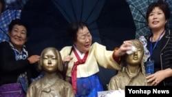 22일 제막식에 참석한 위안부 피해자 한국 이용수(88) 할머니가 소녀상의 얼굴을 닦아주고 있다.