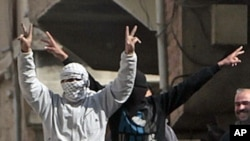Anti-Syrian government protesters flash V-victory signs in the southern city of Daraa, March 23, 2011