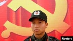 Một cảnh sát đứng phía trước tấm áp phích biểu tượng cộng sản bên ngoài Trung tâm Hội nghị Quốc gia, Hà Nội ngày 15/1/2011.
