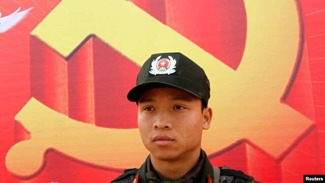 Một cảnh sát đứng canh ở phía trước tấm áp phích  biểu tượng cộng sản bên ngoài Trung tâm Hội nghị Quốc gia.