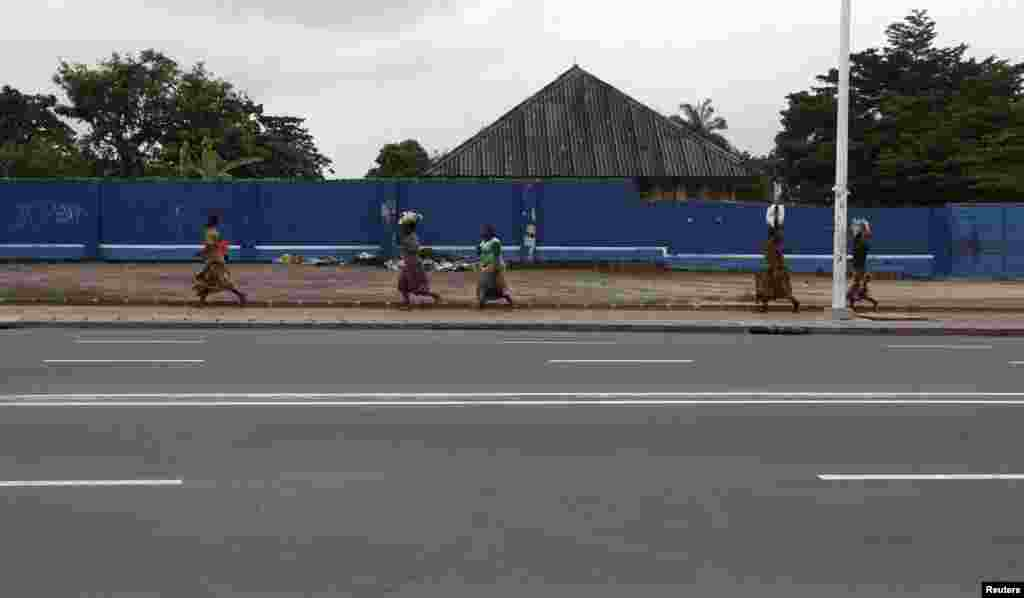 Congolese women run for safety along a deserted street during a clash near the state television headquarters in Kinshasa, Dec. 30, 2013.