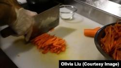 Ekber Kayser, chef and owner of Dolan Uyghur Restaurant, slices carrots before he makes polo.