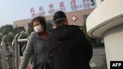 Seorang perempuan (kiri) meninggalkan Pusat Kesehatan Wuhan, di mana seorang pria yang dirawat karena penyakit pernafasan, meninggal, di Kota Wuhan, Provinsi Hubei, 12 Januari 2020. (Foto: AFP)