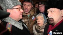 FILE - A police officer talks to leading opposition figure Boris Nemtsov (2nd L) and human rights activist and Moscow Helsinki group chairperson Lyudmila Alekseyeva (2nd R) during a rally in central Moscow January 31, 2010.