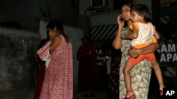 Local women who rushed outdoors following tremors speak on their cellphones, in Kolkata, India, April 13, 2016. A strong earthquake struck Myanmar on Wednesday night and was felt in parts of eastern India and Bangladesh.