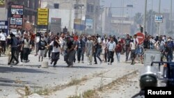 Supporters of Islamist group Ansar al-Sharia clash with riot police at Hai al-Tadamon in Tunis, May 19, 2013.